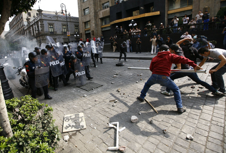 Photo - Protestors attempt to intimidate riot police with a pole in the streets of downtown Mexico City, Saturday, Dec. 1, 2012.  Protests against Mexico's newly sworn-in President Enrique Pena Nieto began early Saturday morning with violent confrontations in the streets and protest speeches from opposition parties inside the congress. Protestors continued through the afternoon, vandalizing downtown businesses, smashing storefront glass windows and setting office furniture ablaze.  (AP Photo/Marco Ugarte)