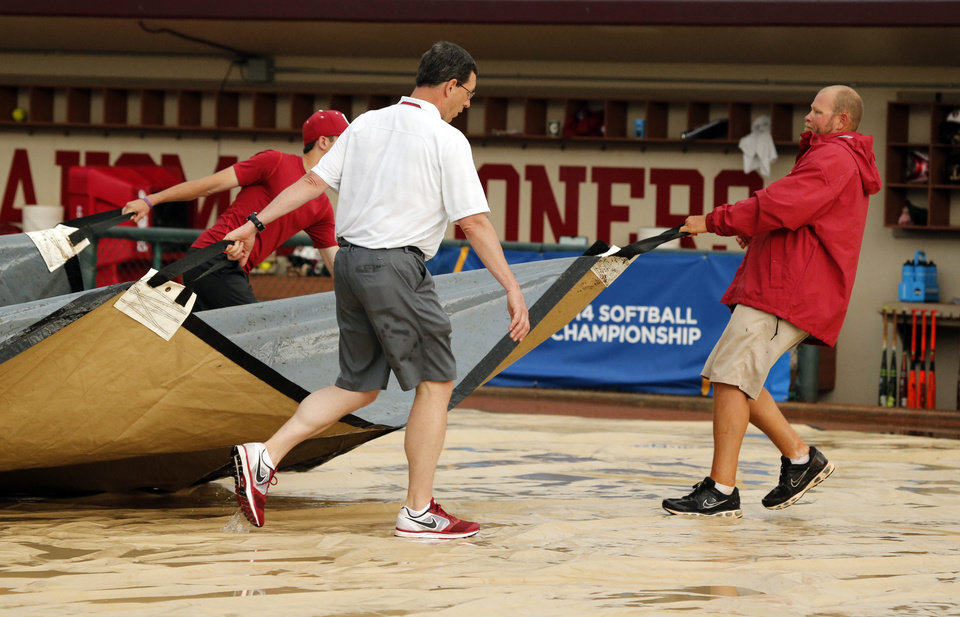Photo - Kenny Mossman, Sr. Associate Athletic Director, left, and groundskeeper Jason Wheeler move the infield cover to shed accumulated water during a lightning and storm delay as the University of Oklahoma Sooner (OU) softball team plays Tennessee in game two of the NCAA super regional at Marita Hynes Field on May 24, 2014 in Norman, Okla. Photo by Steve Sisney, The Oklahoman
