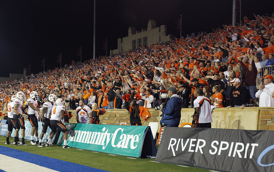 Photo - Oklahoma State fans celebrate after a Cowboy touchdown during a college football game between the Oklahoma State University Cowboys and the University of Tulsa Golden Hurricane at H.A. Chapman Stadium in Tulsa, Okla., Saturday, Sept. 17, 2011. Fans stuck around after a three hour weather delay to see the Cowboys start playing after midnight. Photo by Chris Landsberger, The Oklahoman