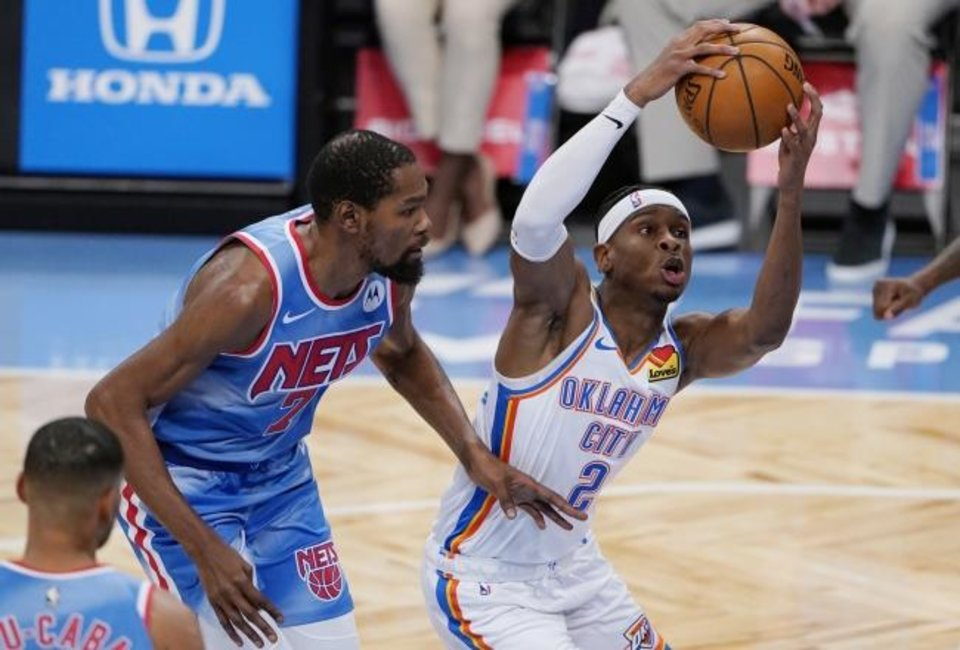 Photo -  Thunder guard Shai Gilgeous-Alexander (2) drives past Nets forward Kevin Durant in the first quarter of OKC's win Sunday in New York. [AP Photo/Kathy Willens]