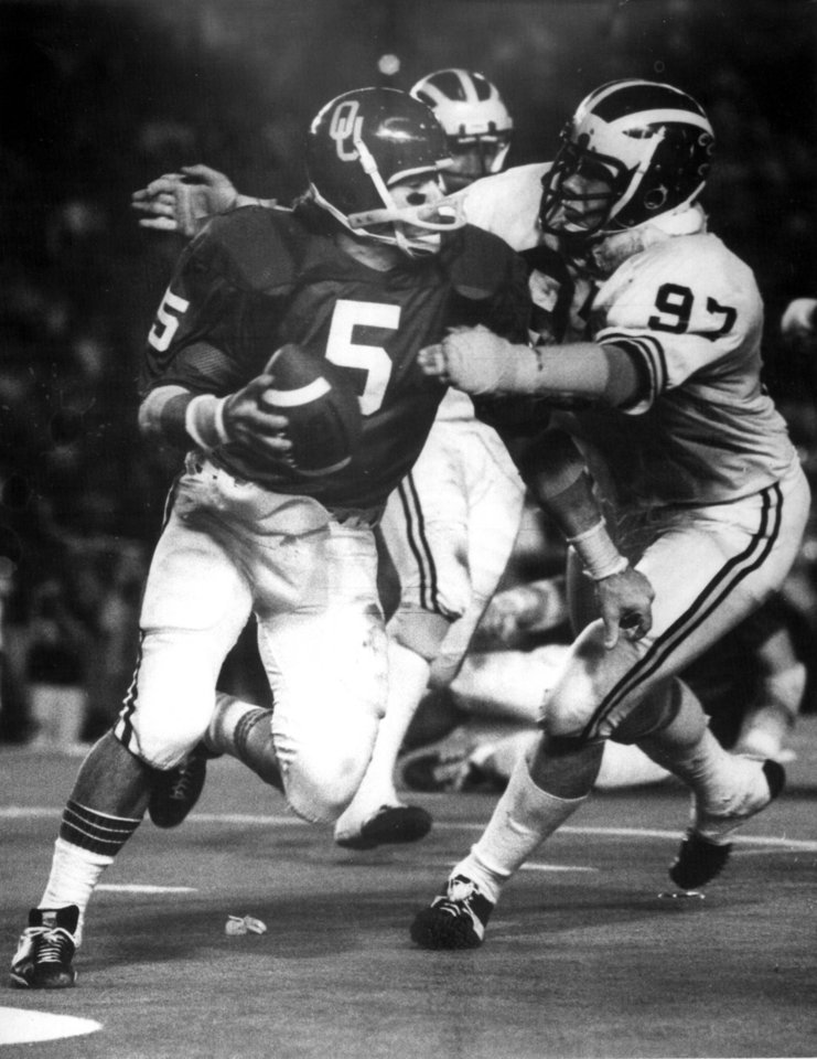 1/1/76. Orange Bowl. OU vs Michigan. COLLEGE FOOTBALL / UNIVERSITY OF OKLAHOMA: OU quarterback Steve Davis tries to escape the grasp of Michighan\'s Jeff Perlinger as the Sooners defeated the Wolverines 14-6 in Miami. Staff photo taken 1/1/76; photo ran in the 1/2/76 Daily Oklahoman. File: Football/OU/OU-Michigan/Orange Bowl/Steve Davis/1976