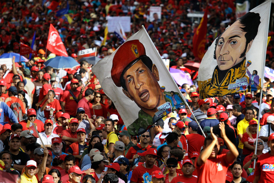 FILE - In this Jan. 10, 2013 file photo, supporters of Venezuela's President Hugo Chavez wave a flag decorated with an image of him wearing military fatigues, and another flag of Venezuela's independence hero Simon Bolivar at Chavez's symbolic inauguration outside Miraflores presidential palace in Caracas, Venezuela. Like much of the country, the armed forces have been left in limbo as the nation awaits the outcome of Chavez�s fourth cancer surgery, carried out last month in a Cuban hospital. He hasn�t appeared or spoken in public since. (AP Photo/Fernando Llano, File)
