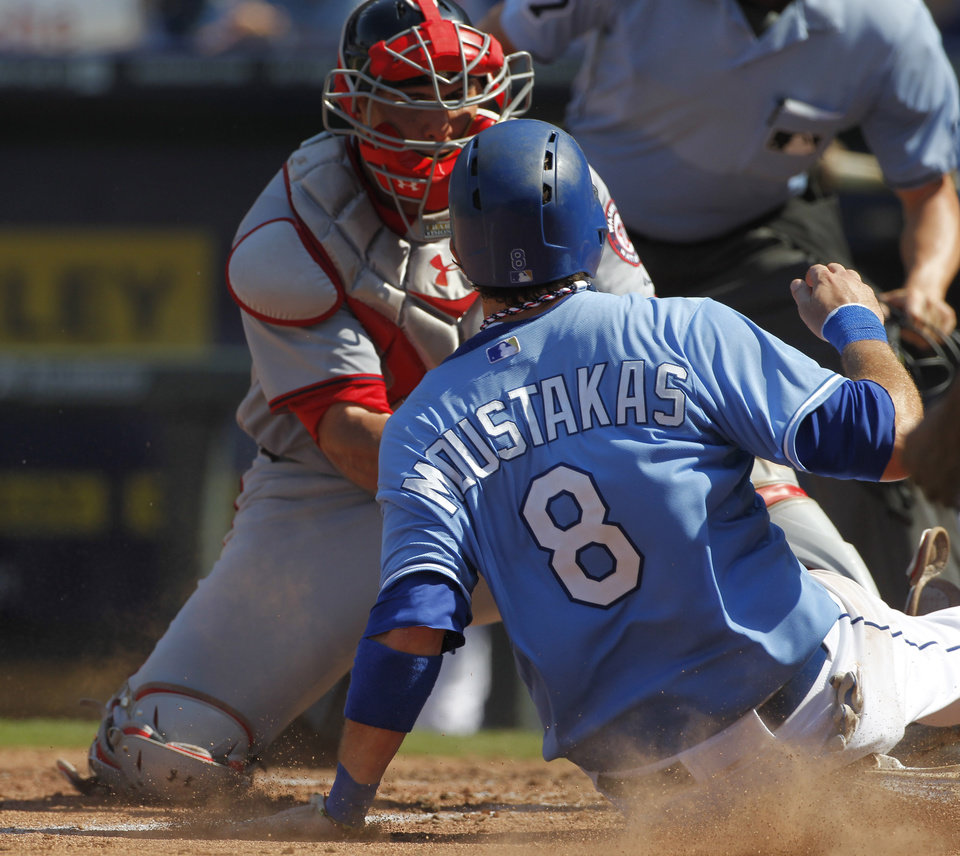 Photo - Kansas City Royals' Mike Moustakas (8) is tagged out at home plate by Washington Nationals catcher Wilson Ramos in the eighth inniing of a baseball game at Kauffman Stadium in Kansas City, Mo., Sunday, Aug. 25, 2013. (AP Photo/Colin E. Braley)