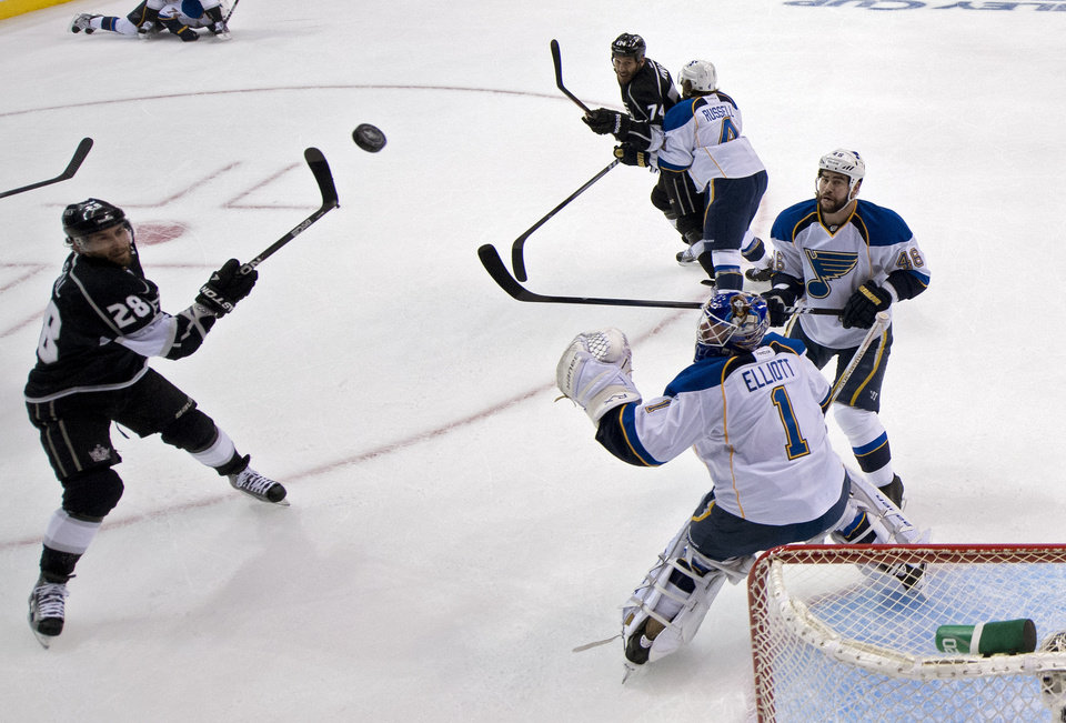 Photo -   Los Angeles Kings center Jarret Stoll, left, reaches for a puck as St. Louis Blues goalie Brian Elliott, lower right, looks on along with defenseman Roman Polak of the Czech Republic during the third period in Game 3 of an NHL hockey Stanley Cup second-round playoff series, Thursday, May 3, 2012, in Los Angeles. The Kings won 4-2. (AP Photo/Mark J. Terrill)