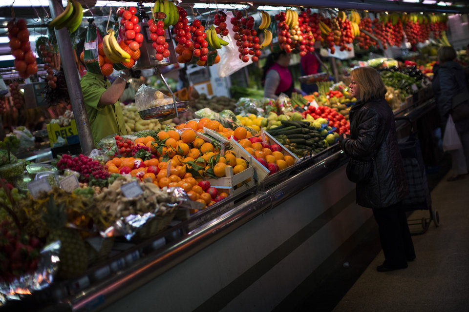 Photo - FILE - In this Thursday Jan. 17, 2013 file photo, a woman buys fruit at a market in Barcelona, Spain. Mediterranean diets have long been touted as heart-healthy, but that's based on observational studies. Now, one of the longest and most scientific tests suggests this style of eating can cut the chance of suffering heart-related problems, especially strokes, in older people at high risk of them. The study lasted five years and involved about 7,500 people in Spain. Results were published online Monday, Feb. 25, 2013 by the New England Journal of Medicine. (AP Photo/Emilio Morenatti)
