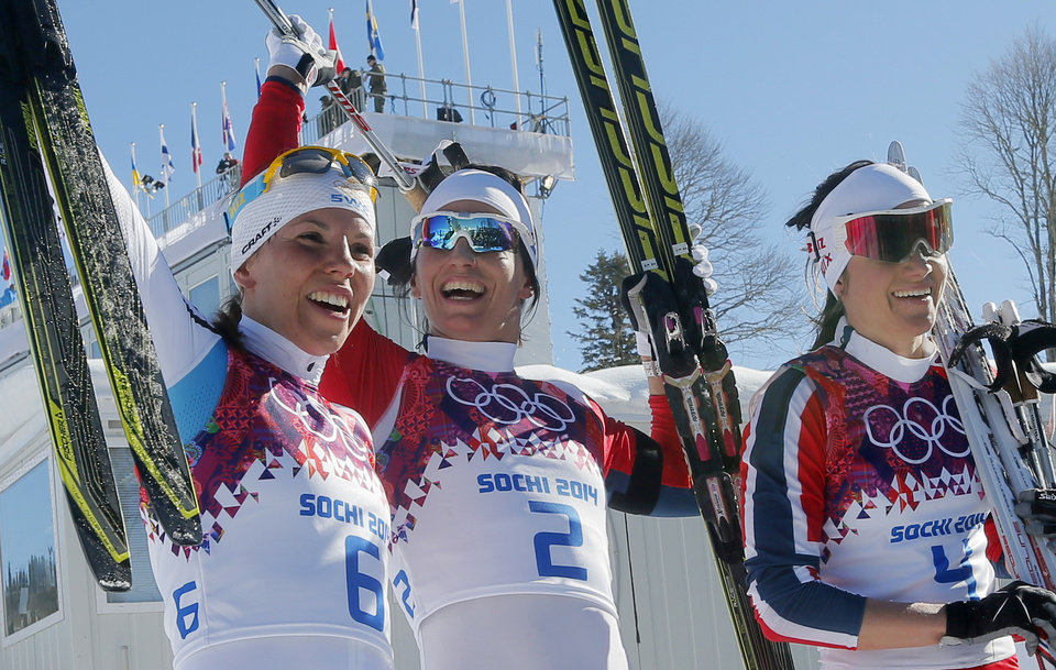 Photo - Norway's gold medal winner Marit Bjoergen is flanked by Sweden's silver medal winner Charlotte Kalla, left, and Norway's bronze medal winner Heidi Weng after the flower ceremony for the women's cross-country 15k skiathlon at the 2014 Winter Olympics, Saturday, Feb. 8, 2014, in Krasnaya Polyana, Russia. (AP Photo/Dmitry Lovetsky)