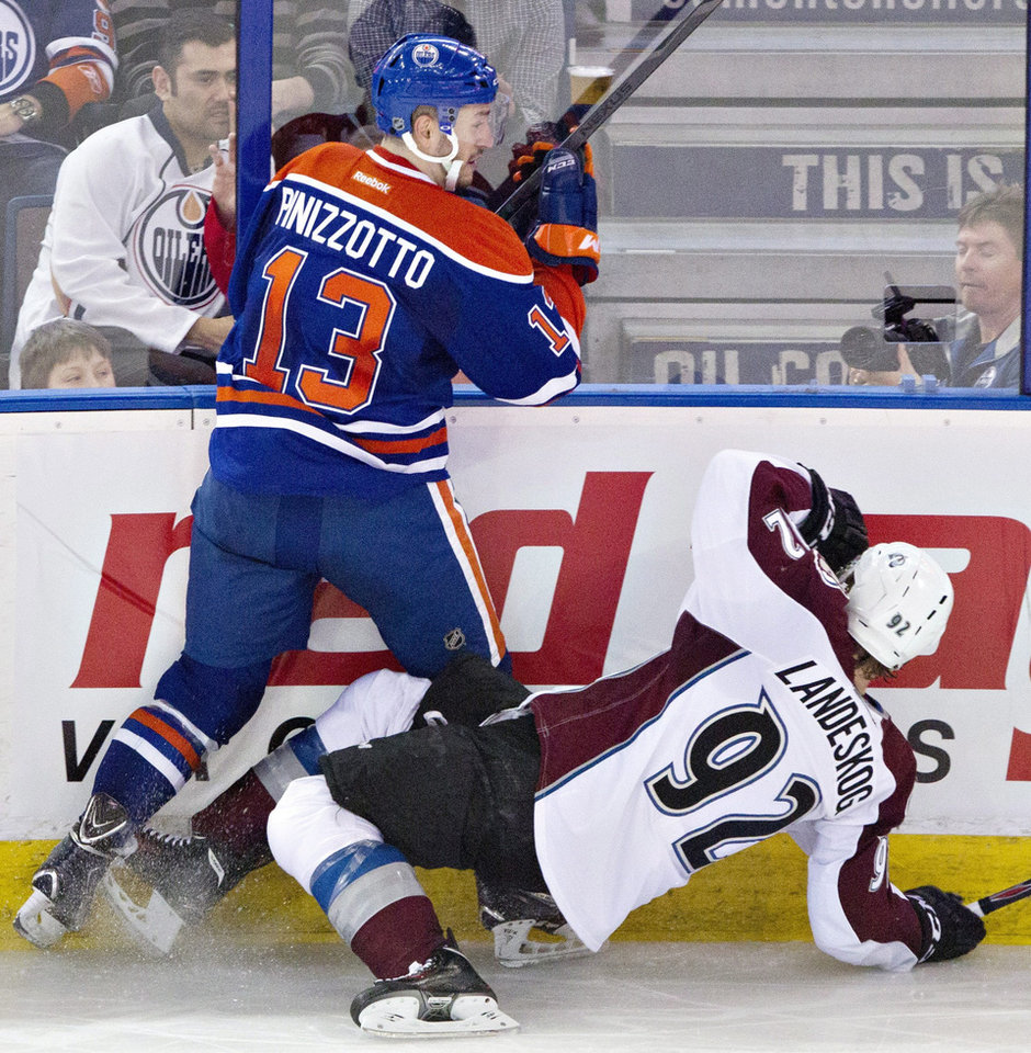 Photo - Colorado Avalanche's Gabriel Landeskog (92) is checked by Edmonton Oilers' Steven Pinizzotto (13) during second period NHL hockey action in Edmonton,  Alberta, on Tuesday April 8, 2014. (AP Photo/The Canadian Press, Jason Franson)