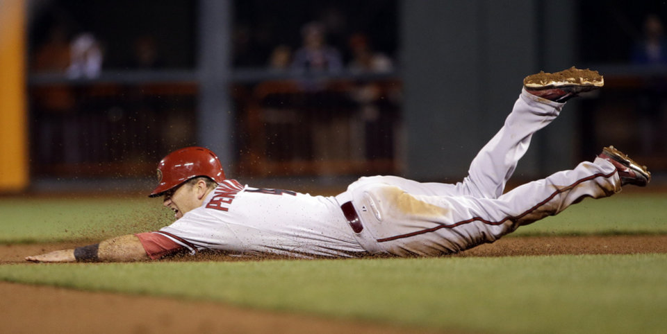 Photo - Arizona Diamondbacks' Cliff Pennington  steals second base against the San Francisco Giants during the 10th inning of a baseball game on Thursday, April 10, 2014, in San Francisco. Pennington would then score the go-ahead run on a single by Tony Campana. Arizona won 6-5. (AP Photo/Marcio Jose Sanchez)