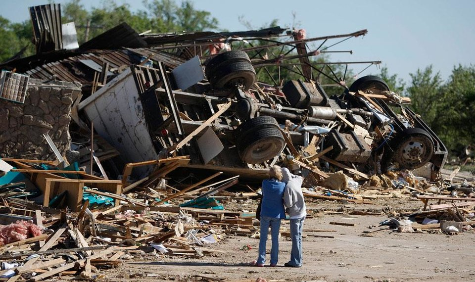 Photo -  People stand by the remains of a business after a tornado struck Woodward, Okla., Sunday, April 15, 2012. Photo by Bryan Terry