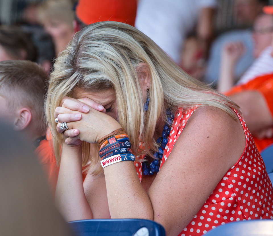 Photo - Cindy O'Connor, wife of Virginia head coach Brian O'Connor, drops her head onto her hands after Vanderbilt loaded the bases in the top of the third inning as the University of Virginia takes on Vanderbilt University in the first game of the championship series in the 2014 Men's College World Series at TD Ameritrade Park in Omaha, Neb. on Monday, June 23, 2014. (AP Photo/The Omaha World-Herald, Kent Sievers) MAGS OUT TV OUT