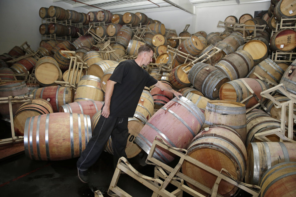 Photo - Cellar worker Daniel Nelson looks over toppled barrels of Cabernet Sauvignon following an earthquake at the B.R. Cohn Winery barrel storage facility Sunday, Aug. 24, 2014, in Napa, Calif. Winemakers in California's storied Napa Valley woke up to thousands of broken bottles, barrels and gallons of ruined wine as a result of Sunday's earthquake.  (AP Photo/Eric Risberg)