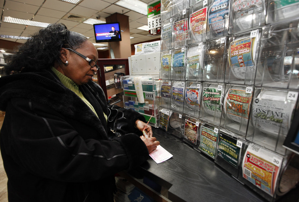 Photo - Donna Fields picks her Powerball numbers in Detroit, Wednesday, Nov. 28, 2012. Fields picked two sets of numbers off the top of her head and two easy picks in tonight's Powerball total with an estimated 500 million dollar jackpot. Fields said,