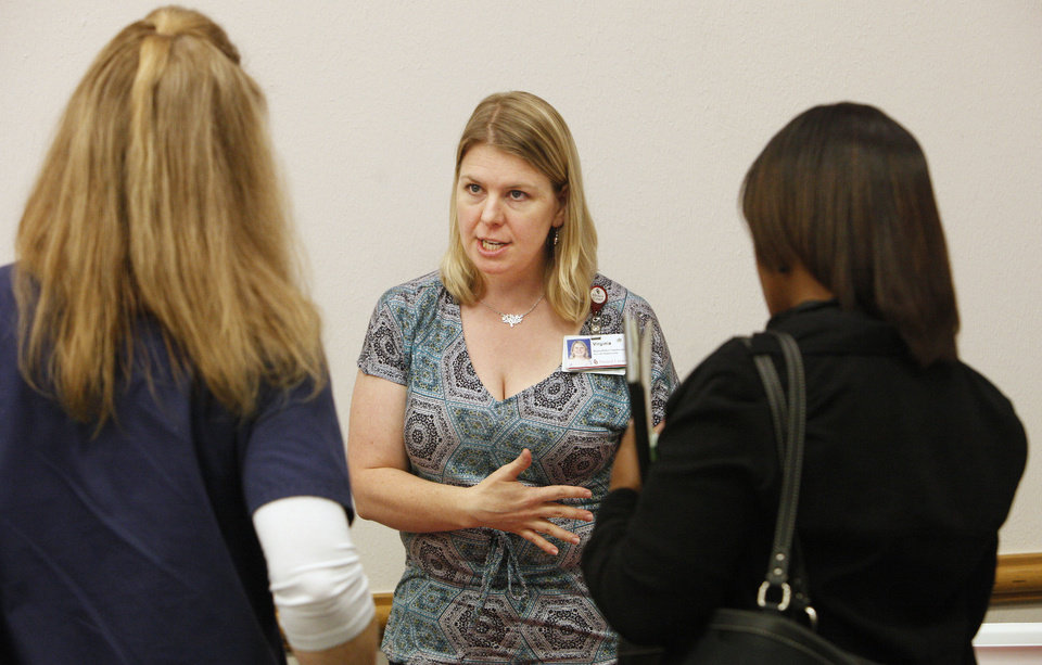 Photo - Virginia Oden, a recruiter with the University of Oklahoma Medical Center, talks with students Oklahoma City Community College's annual job fair. Retailers and other companies are ramping up hiring for the holidays.  PAUL B. SOUTHERLAND - PAUL B. SOUTHERLAND
