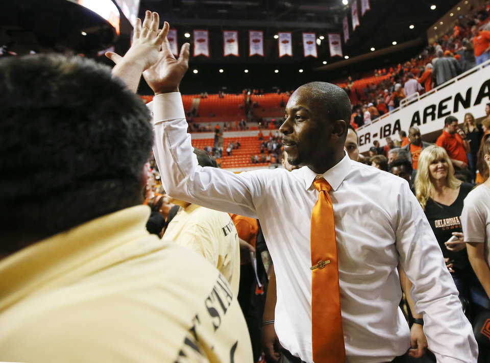 Photo - OSU head coach Mike Boynton gives a fan a high five after a Bedlam men's college basketball game between the Oklahoma Sooners (OU) and the Oklahoma State Cowboys (OSU) at Gallagher-Iba Arena in Stillwater, Okla., Saturday, Jan. 20, 2018. OSU won 83-81 in overtime. Photo by Nate Billings, The Oklahoman