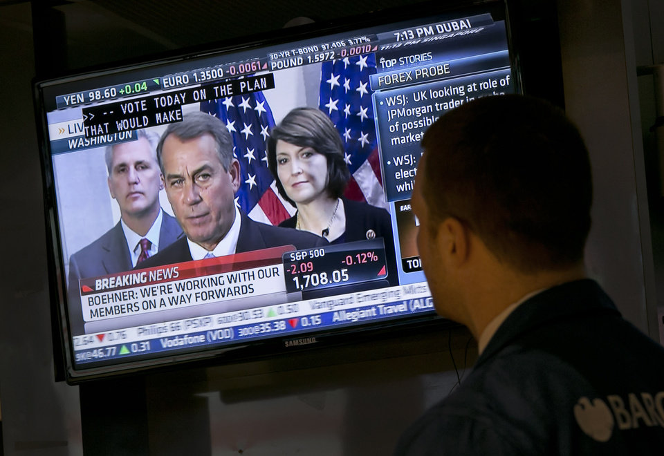 Photo - Specialist Frank Masiello watches a television monitor on the floor of the New York Stock Exchange showing a Washington news conference by House Speaker John Boehner, Tuesday, Oct. 15, 2013. Leaders in the House of Representatives and Senate were negotiating separate but similar plans Tuesday to reopen the U.S. government and prevent a default on American debt that economists say could tip the global economy back into recession. (AP Photo/Richard Drew)