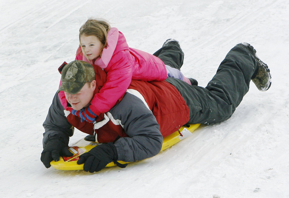 Photo - Five year old Kyleigh Tood takes a ride on her father Mike's back as they sled at Will Rogers Park in Oklahoma City, OK, Saturday, Jan. 30, 2010. By Paul Hellstern, The Oklahoman