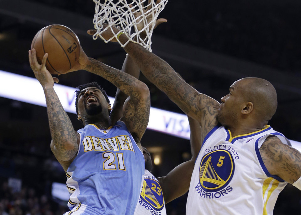 Photo - Denver Nuggets' Wilson Chandler (21) drives for a shot over Golden State Warriors' Marreese Speights, right, during the first half of an NBA basketball game Wednesday, Jan. 15, 2014, in Oakland, Calif. (AP Photo/Ben Margot)