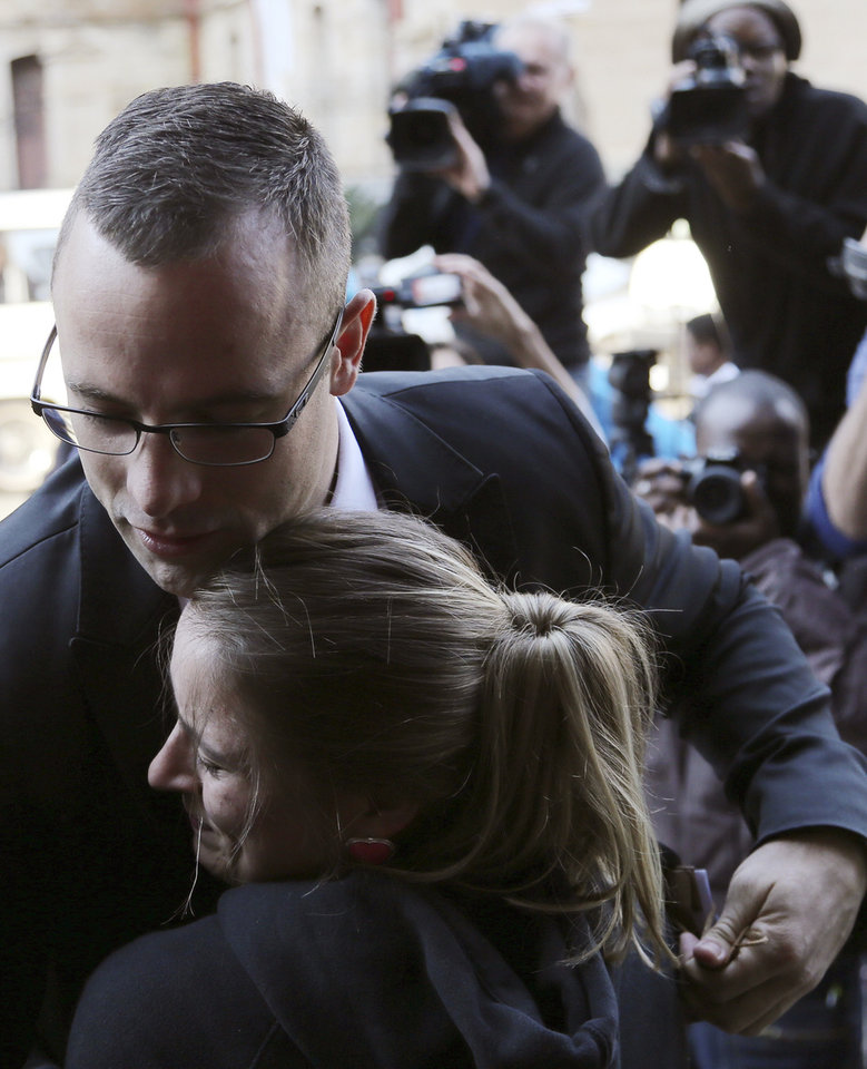 Photo - Oscar Pistorius, top, receives a hug from his fan Kayla Nolan as he arrives at the high court in Pretoria, South Africa, Monday, May 5, 2014. Pistorius' murder trial enters a critical phase Monday as his defense team attempts to recover from a faltering start and reinforce the disabled athlete's claim that he fatally shot girlfriend Reeva Steenkamp by mistake because he was overwhelmed by a long-held fear of violent crime. (AP Photo/Themba Hadebe)