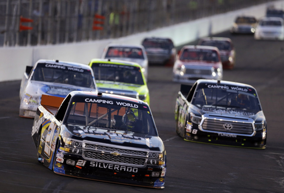 Photo - DrJoey Coulter (21) and others make their way around the track during the NASCAR Truck Series auto race at Gateway Motorsports Park on Saturday, June 14, 2014, in Madison, Ill. (AP Photo/Jeff Roberson)