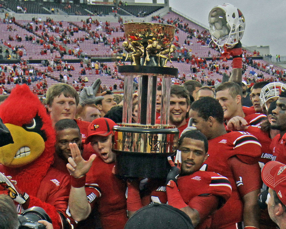 Photo -   Louisville players celebrate with the Governor's Cup trophy after defeating Kentucky 32-14 in an NCAA college football game at Cardinal Stadium in Louisville, Ky., Sunday, Sept. 2, 2012. (AP Photo/Garry Jones)