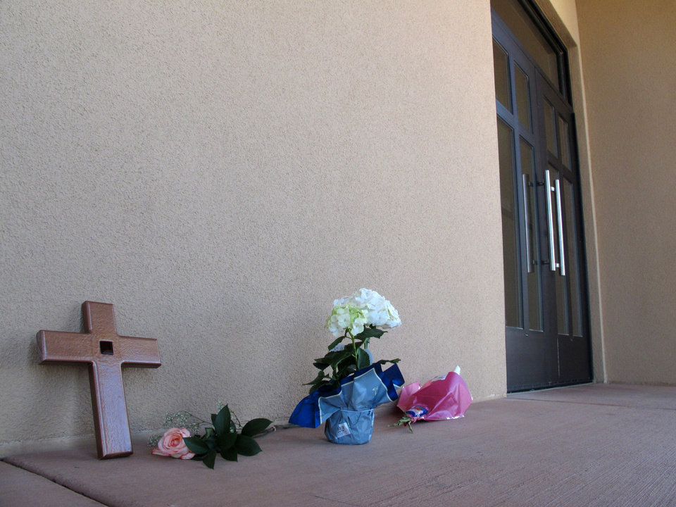 Photo - A cross and flowers are left outside Monday, April 29, 2013 by a parishioner at the St. Jude Thaddeus Catholic Church in Albuquerque a day after a man stabbed several churchgoers Sunday as Mass was ending. Police say four parishioners were injured, including church choir director Adam Alvarez, but none have life-threatening injuries. Lawrence Capener, 24, is charged with three counts of aggravated battery and is being held on $75,000 bail. (AP Photo/Russell Contreras)