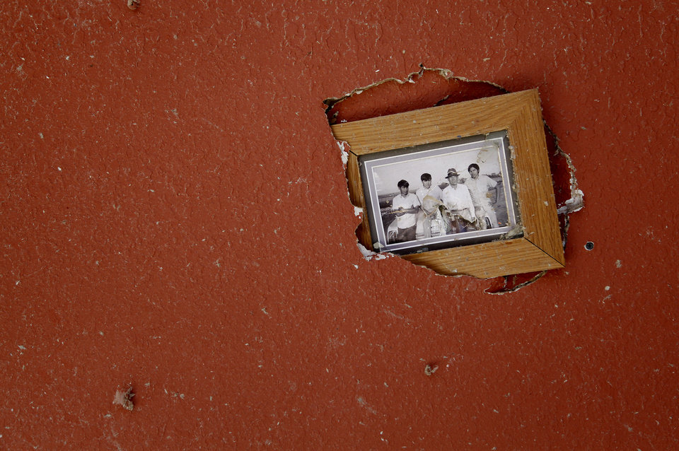Photo - A family photo is stuck through the wall in the home of Robert Todd west of El Reno, Wednesday, May 25, 2011. Photo by Chris Landsberger, The Oklahoman