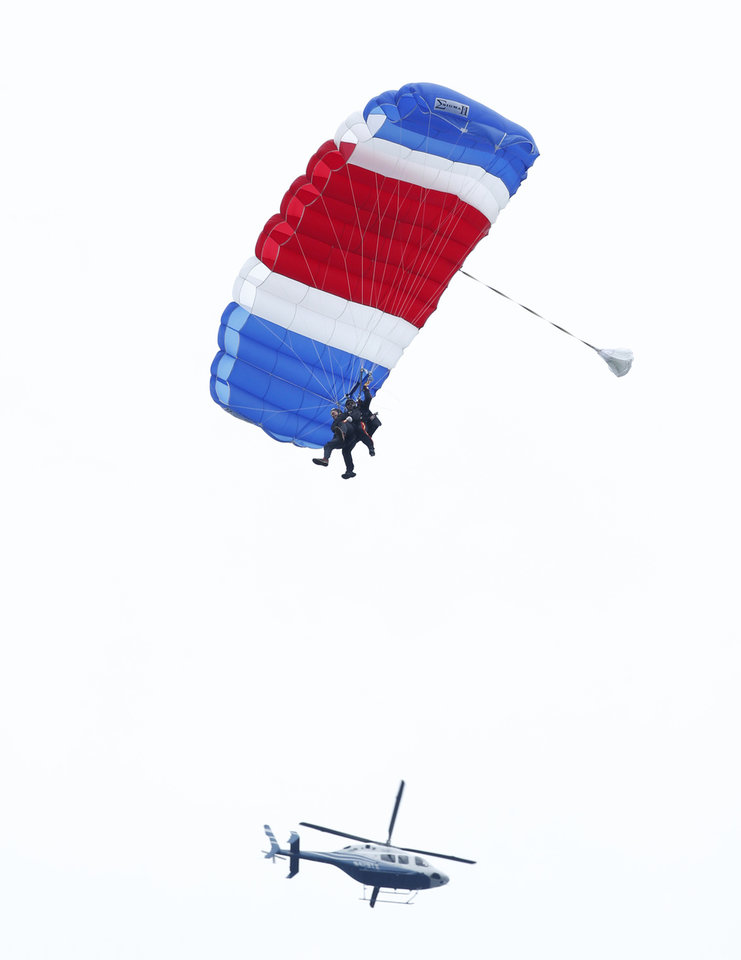 Photo - Former President George H.W. Bush, strapped to Sgt. 1st Class Mike Elliott, a retired member of the Army's Golden Knights parachute team, float to the ground during a tandem parachute jump near Bush's summer home in Kennebunkport, Maine, Thursday, June 12, 2014. Bush made the jump, his eighth, in celebration of his 90th birthday. (AP Photo/Robert F. Bukaty)