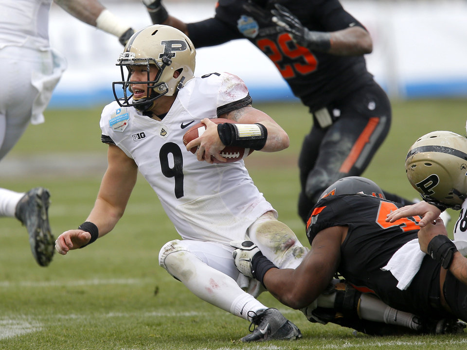 Photo - Oklahoma State's Tyler Johnson (40) brings down Purdue's Robert Marve (9) during the Heart of Dallas Bowl football game between Oklahoma State University and Purdue University at the Cotton Bowl in Dallas, Tuesday, Jan. 1, 2013. Oklahoma State won 58-14. Photo by Bryan Terry, The Oklahoman