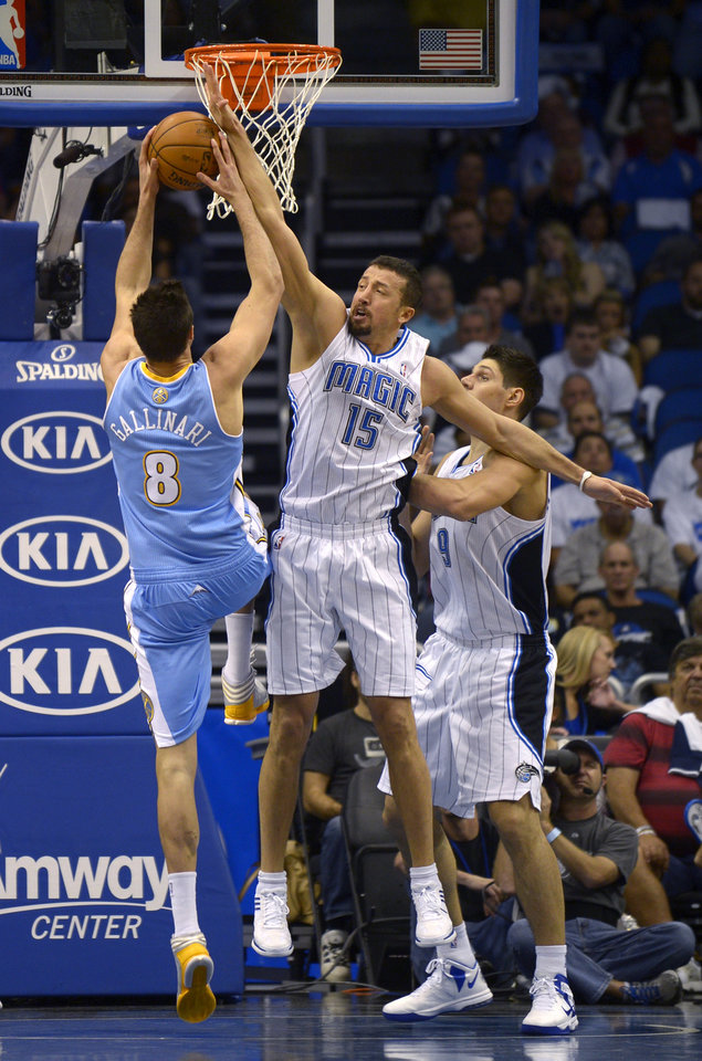 Orlando Magic forward Hedo Turkoglu (15), of Turkey, attempts to block a shot by Denver Nuggets forward Danilo Gallinari (8), of Italy, as Nikola Vucevic, right, of Montenegro, watches during the first half of an NBA basketball game in Orlando, Fla., Friday, Nov. 2, 2012. The Magic won 102-89. (AP Photo/Phelan M. Ebenhack)