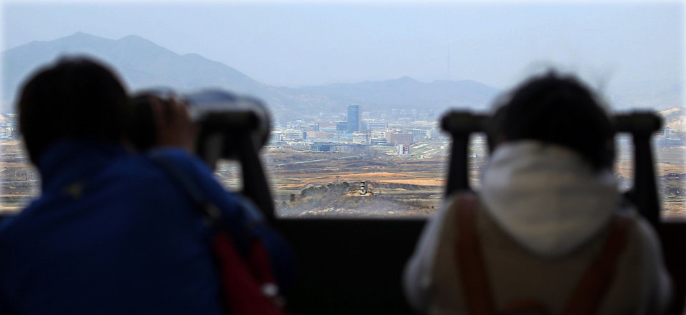Photo - Visitors look over the North-South Korea industrial complex in Kaesong, North Korea, through binoculars at Dora Observation Post in the demilitarized zone (DMZ) near the border village of Panmunjom, in Paju, South Korea, Tuesday, April 9, 2013. The massive industrial park the rival Koreas have jointly run for nearly decade was a virtual ghost town Tuesday, its South Korean managers left to wander past shutdown assembly lines or stuff their cars to the brim with whatever goods would fit before heading south for the Demilitarized Zone that divides the nations. (AP Photo/Won Dae-hyun)  KOREA OUT