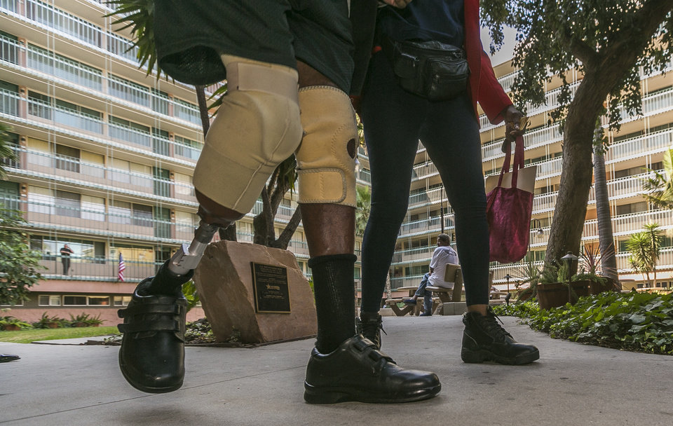 Photo - U.S. Veteran Revell Tweedle, left, and his wife, Ruth Tweedle walk past the Los Angeles Westside Residences central court in Inglewood, Calif., Wednesday, Sept. 11, 2013. A Los Angeles International Airport security screener, Nna Alpha Onuoha, 29, not seen, was arrested hours after quitting his job for making unspecified threats referencing Wednesday's Sept. 11 anniversary and calling airport officials and telling them to evacuate terminals, the FBI said. Onuoha's apartment at the Westside Residences near LAX, found no dangerous materials but did turn up a note containing unspecified threats that cited the anniversary of the Sept. 11, 2001, attacks, authorities said. (AP Photo/Damian Dovarganes)