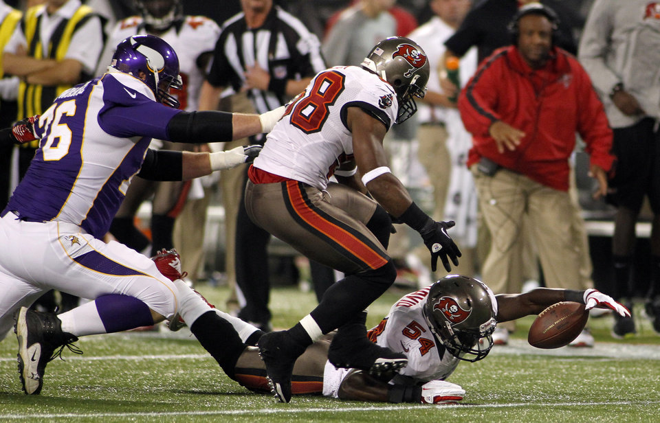 Photo -   Tampa Bay Buccaneers outside linebacker Lavonte David (54) and teammate Quincy Black, center, look to recover a fumble in front of Minnesota Vikings tackle Geoff Schwartz, left, during the first half of an NFL football game Thursday, Oct. 25, 2012, in Minneapolis. The Buccaneers recovered the ball. (AP Photo/Andy King)