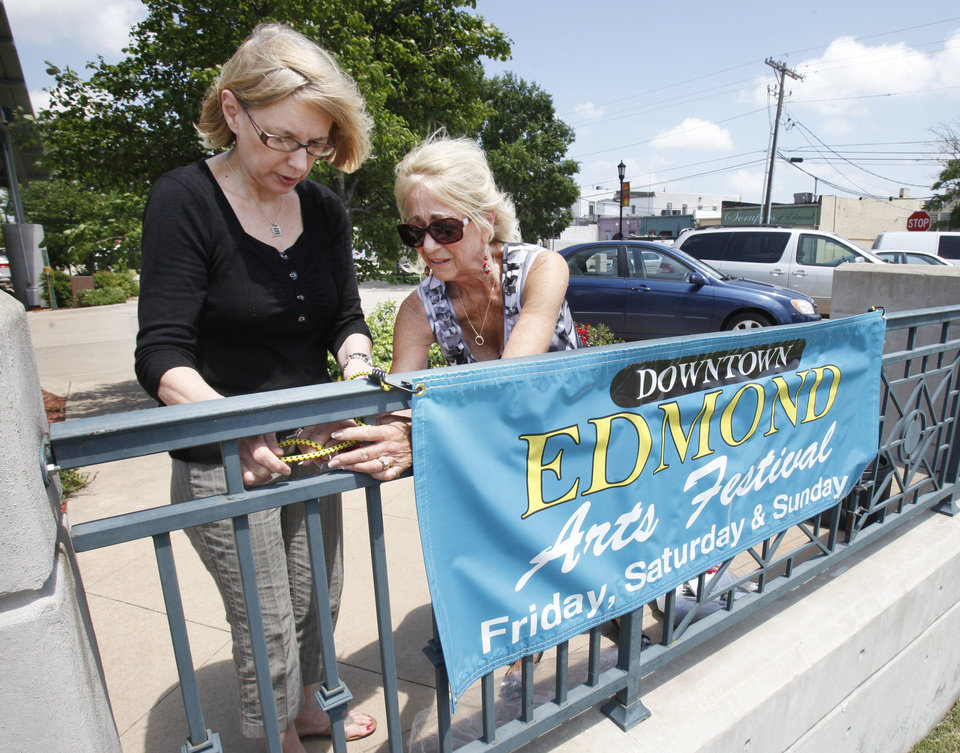 Mary Edwards, Downtown Edmond Business Association president, left, and festival co-director, Bryanne Wallace, put up a sign for this year's Edmond Downtown Arts Festival. PHOTO BY PAUL HELLSTERN, THE OKLAHOMAN