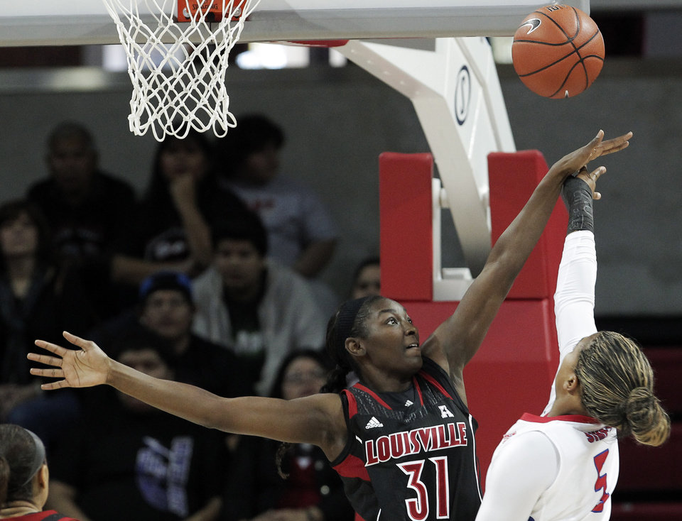 Photo - SMU forward Akil Simpson (5) attempts to shoot as Louisville's Asia Taylor (31) defends in the first half of an NCAA college basketball game on Sunday, Jan. 19, 2014, in Dallas. (AP Photo/Brandon Wade)