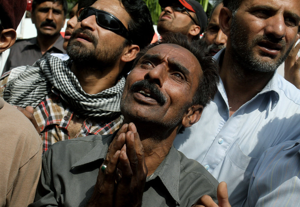 Photo - Pakistanis pray for people stranded in a building that caught on fire, not pictured, in Lahore, Pakistan, Thursday, May 9, 2013. The 13-storey government building caught fire and quickly intensified spreading to three floors of the tall building. (AP Photo/K.M. Chaudary)