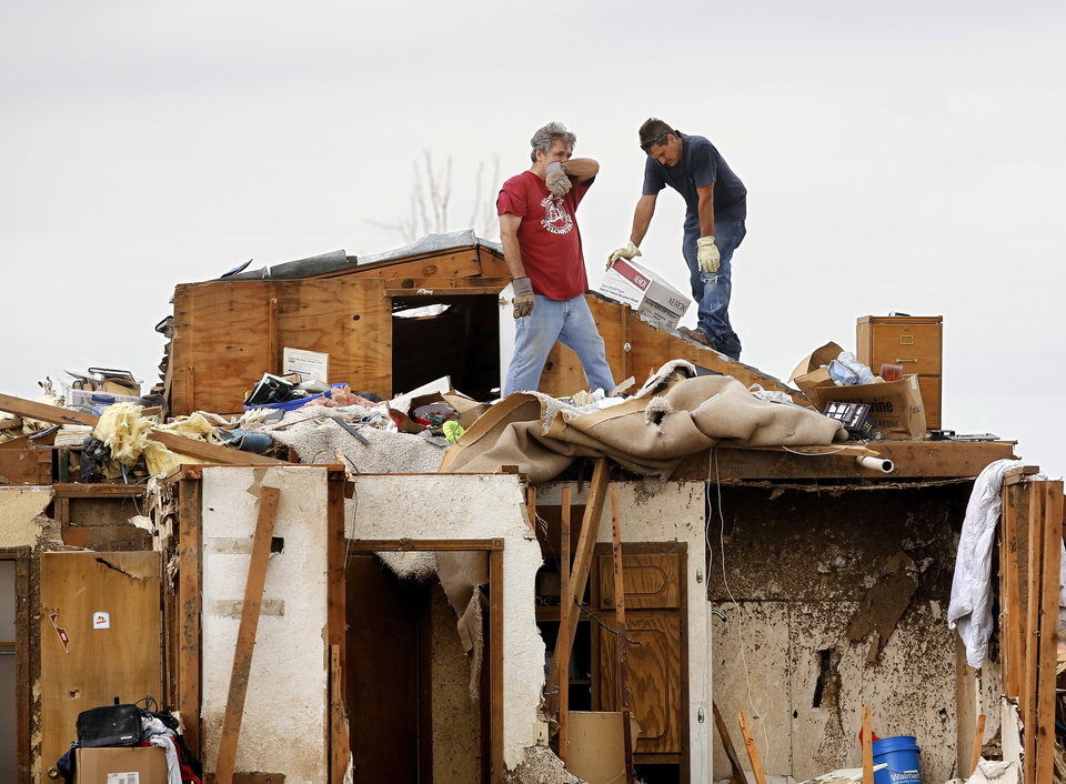 Photo - Two men work in an upstairs section of this home which had its roof taken off. The home is west of Santa Fe, north of SW 19 Street. Volunteers from various parts of the country joined Oklahomans in assisting residents on Saturday,  May 25, 2013, doing whatever was needed to remove debris and salvage items from this neighborhood east of Santa Fe, north of SW 19 Street.  An EF5 tornado leveled many neighborhoods in Moore and southwest Oklahoma City last Monday.   Photo  by Jim Beckel, The Oklahoman.