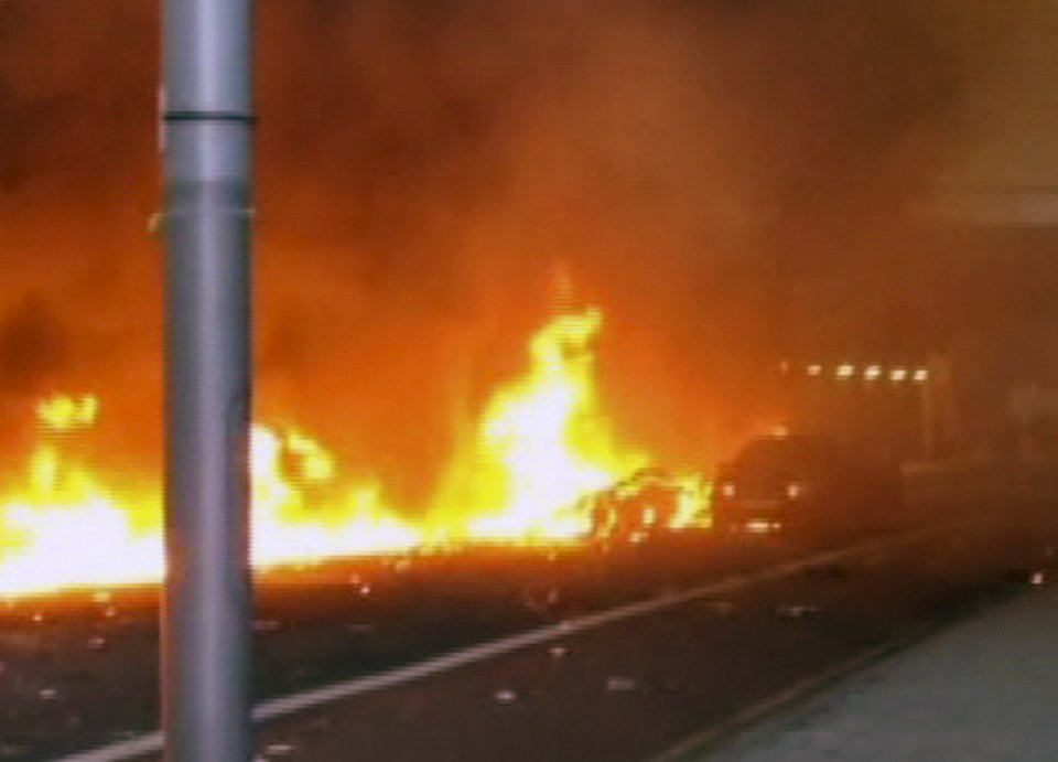 Photo - In this image taken from amateur video, showing a line of flaming debris shortly after a helicopter crash in central London, early Wednesday Jan. 16, 2013.  Police say two people were killed when a helicopter crashed during rush hour in central London after apparently hitting a construction crane on the side of St. George's Tower in the Vauxhall area of central London. (AP Photo / Nic Walker) TV OUT