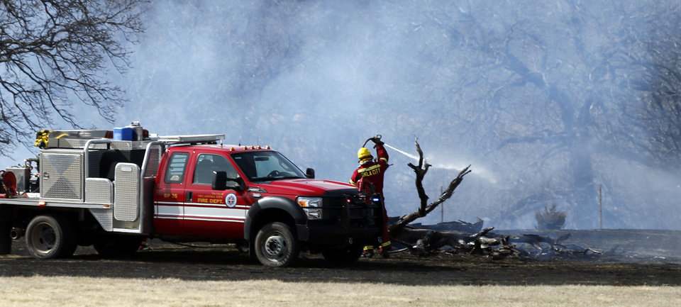 Photo -  Above and below: Firemen put out a grass fire Thursday near SE 74 and S Pottawatomie Road in Oklahoma City. The fire burned across several acres. Photos by Steve Sisney, The Oklahoman   STEVE SISNEY -