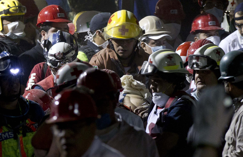 Photo - Rescue workers and firefighters carry an injured person after an explosion in a building at Mexico's state-owned oil company PEMEX complex, in Mexico City, Thursday Jan. 31, 2013. The explosion killed more than 10 people and injured some 80 as it heavily damaged three floors of the building. According to civil protection and local media some people remained trapped in the debris from the explosion, which occurred in the basement of an administrative building next to the iconic, 52-story tower of Petroleos Mexicanos, or PEMEX. (AP Photo/Eduardo Verdugo)