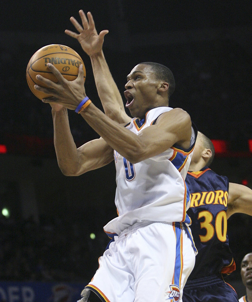 Photo - Oklahoma City Thunder guard Russell Westbrook, left, goes to the basket in front of Golden State guard Stephen Curry, right, in the third quarter of an NBA basketball game in Oklahoma City, Sunday, Jan. 31, 2010. Westbrook had 28 points as Oklahoma City won 112-104. (AP Photo/Sue Ogrocki) ORG XMIT: OKSO112
