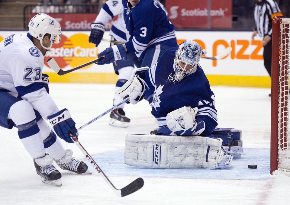 Photo - Toronto Maple Leafs goaltender Jonathan Bernier, right, makes a save on Tampa Bay Lightning right winger J.T. Brown (23) during first period of an NHL game in Toronto, Tuesday, Jan. 28, 2014. (AP Photo/The Canadian Press, Frank Gunn)