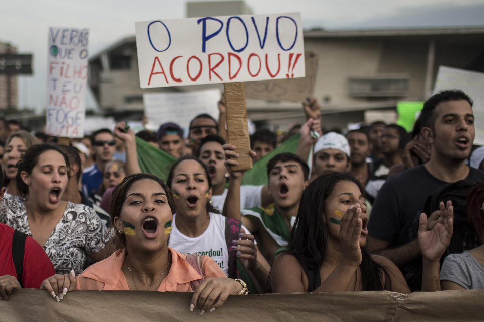 Photo - Residents of the upper middle class neighborhood Barra da Tijuca shout slogans as they hold a banner that reads in Portuguese;