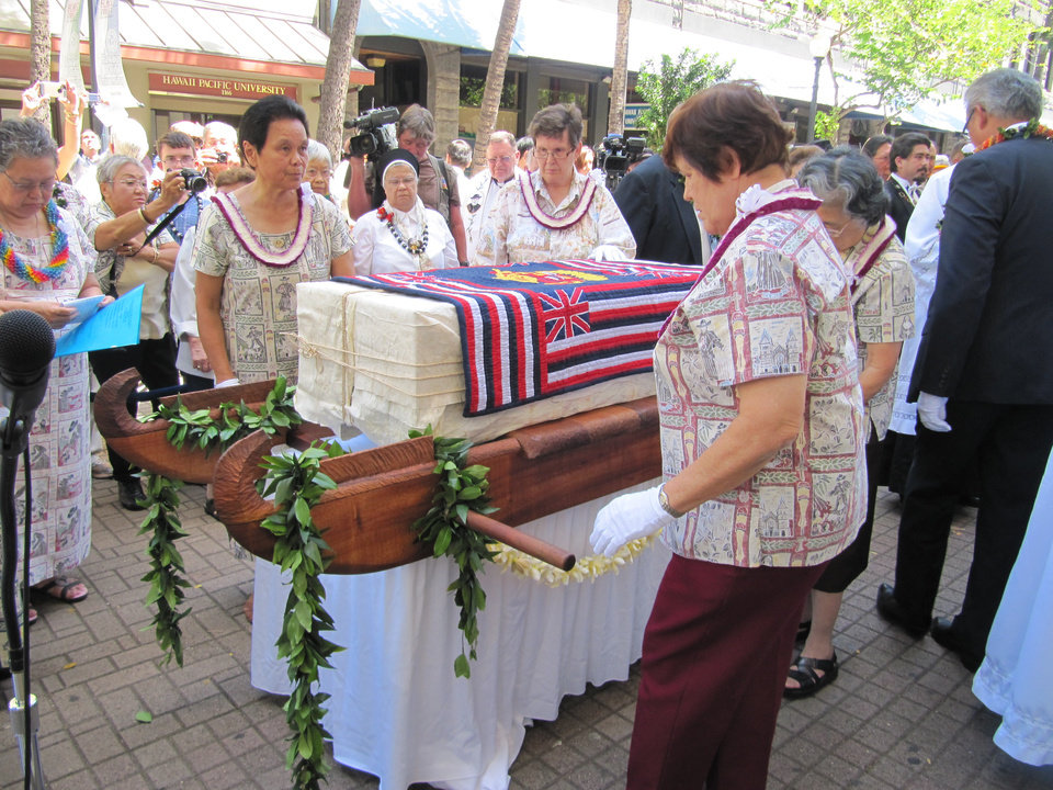 Photo - A casket containing the remains of St. Marianne Cope is prepared for a ceremony and Mass at the Cathedral of Our Lady of Peace in Honolulu, Thursday, July 31, 2014. A sealed zinc-coated metal box containing the bones will be placed upright in a koa wood and glass cabinet in the cathedral. (AP Photo/Marco Garcia)