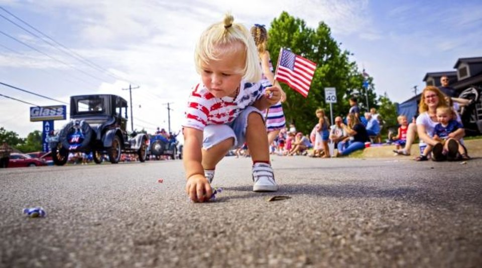 Photo -  Axle Davidson, 2, collects candy Thursday as he carries his American flag during the Bethany Freedom Festival parade.   [Chris Landsberger/The Oklahoman]