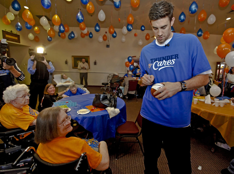 Nick Collison autographs a ball for bingo winner Marta Brown during the Oklahoma City Thunder's 1000th community appearance at Ranchwood Nursing Home on Tuesday, Nov. 27, 2012, in Yukon, Okla.   Photo by Chris Landsberger, The Oklahoman