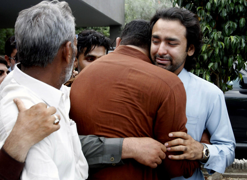 Photo - People comfort Musa Gilani, right, the brother of Ali Haider Gilani who has been kidnapped in Multan, Pakistan, Thursday, May 9, 2013. Gunmen attacked an election rally in Pakistan's southern Punjab province on Thursday and abducted Ali Haider Gilani son of a former prime minister, intensifying what has already been a violent run-up to Saturday's nationwide elections. (AP Photo/Zeeshan Hussain)