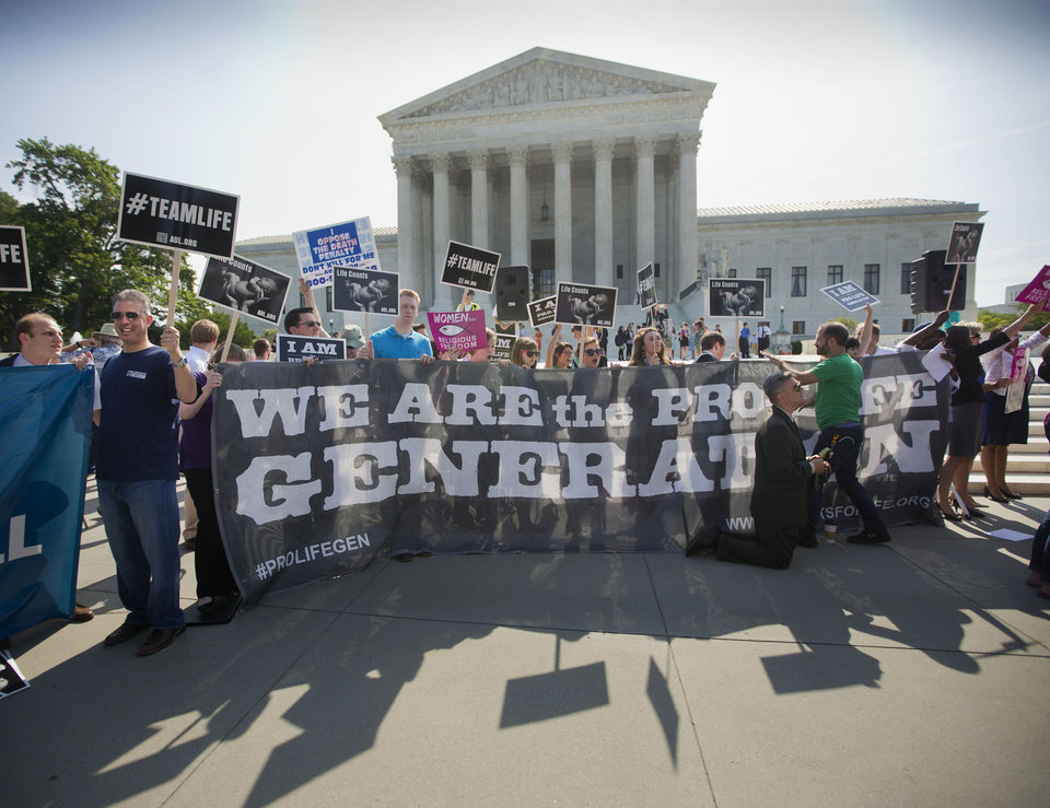 Photo - Demonstrators stand on the steps outside the Supreme Court in Washington, Monday, June 30, 2014. The Supreme Court is poised to deliver its verdict in a case that weighs the religious rights of employers and the right of women to the birth control of their choice. (AP Photo/Pablo Martinez Monsivais)