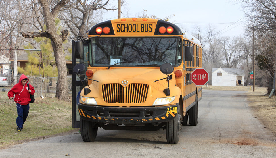 Photo - A student hurries to catch an Oklahoma City Public School bus with its stop sign out and flashing March 7 at Allen Street and Sheridan Avenue in Oklahoma City.  Photo by Paul B. Southerland, The Oklahoman  PAUL B. SOUTHERLAND - PAUL B. SOUTHERLAND