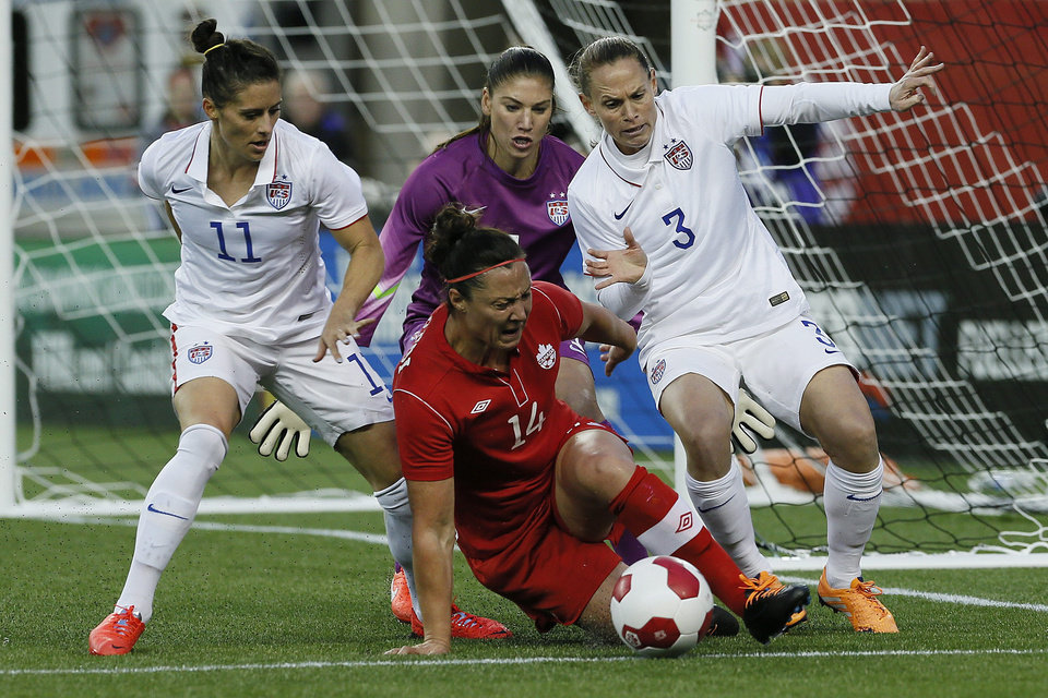 Photo - Canada's forward Melissa Tancredi (14) drives for the net as USA's goalkeeper Hope Solo (1) looks on as defenders Ali Krieger (11) and Christie Rampone (3) defend during the second half soccer of an exhibition soccer match in Winnipeg, Manitoba, Thursday, May 8, 2014. (AP Photo/The Canadian Press, John Woods)
