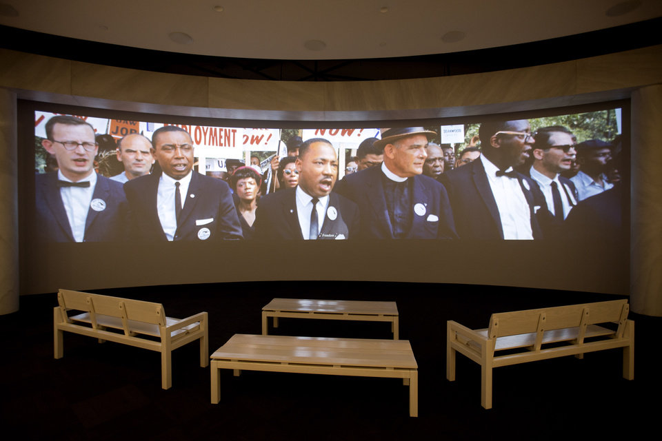 Photo - In this June 16, 2014 photo, a movie plays as part of the March on Washington exhibit at the newly built National Center for Civil and Human Rights in Atlanta. The new museum about the history of civil rights opens next week in Atlanta, the city where Martin Luther King Jr. was based. But the National Center for Civil and Human Rights also explores other human rights struggles, from women's rights and LGBT issues to immigration and child labor. The museum devotes separate galleries to modern human rights issues and the U.S. civil rights movement of the 1950s and '60s, but also demonstrates how the two struggles are related. Visitors learn history through interactive exhibits and stories of real people. (AP Photo/David Goldman)